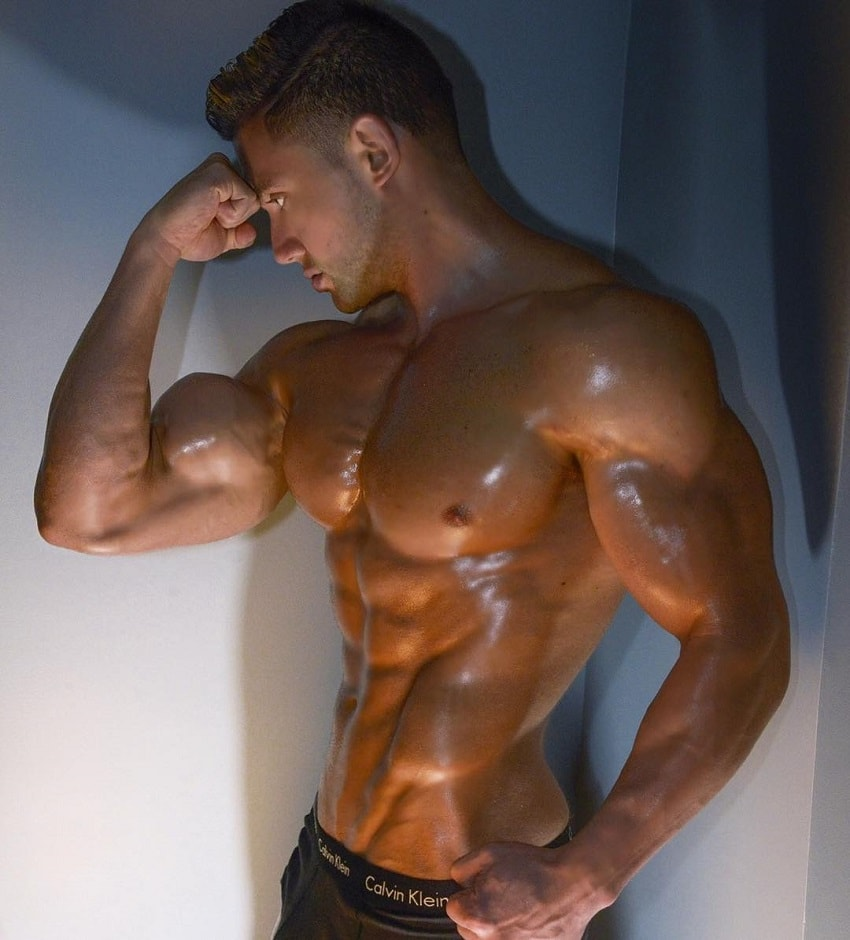Daniel Zukich standing shirtless and oiled-up, looking ripped and big
