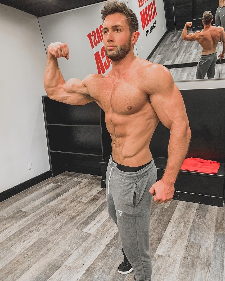 Daniel Zukich flexing his biceps in an empty room