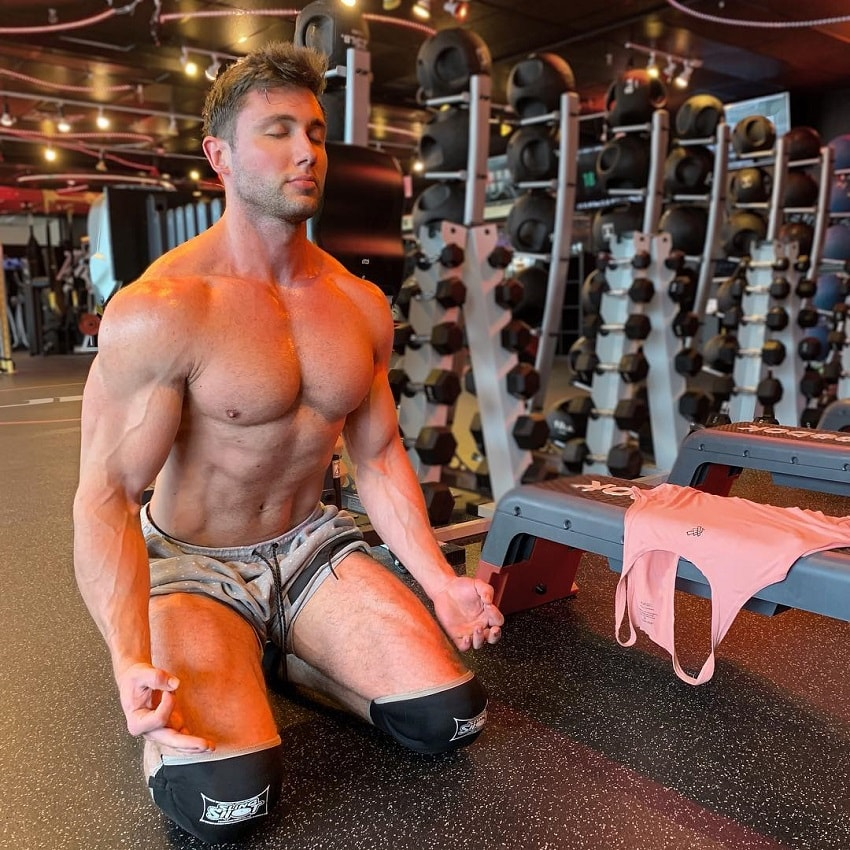 Daniel Zukich kneeling shirtless on the floor in the gym, meditating, looking ripped and big