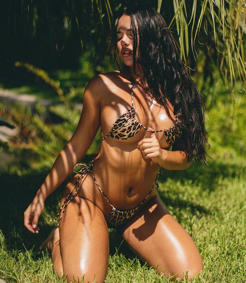 Diana K. Levy kneeling on grass wearing a bikini with panthera stripes looking fit