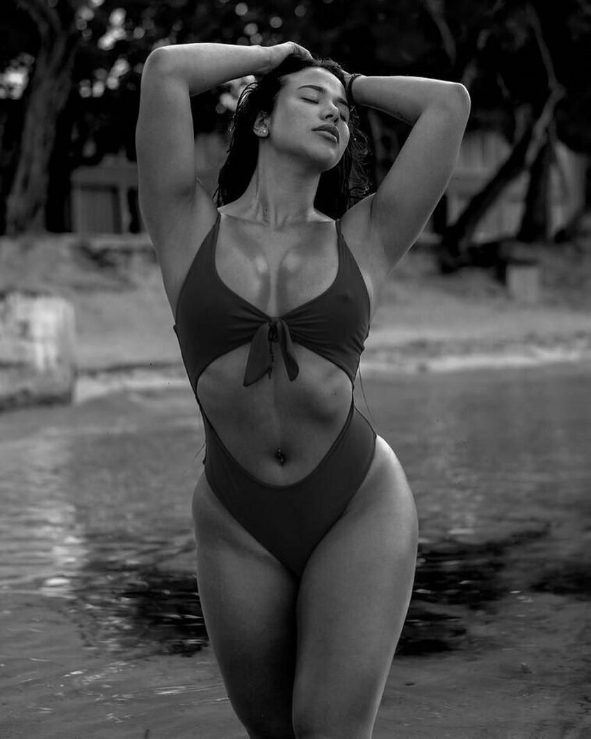 Diana K. Levy posing by the lake in a black and white photo, looking fit and lean