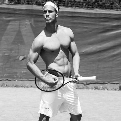 Edoardo Santonocito standing shirtless on a tennis court with a tennis racket in his hand