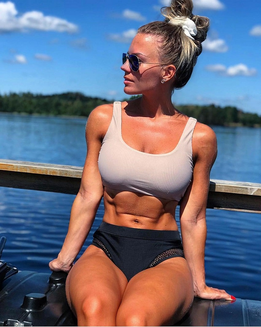 Elin Hedstrom sitting down on a wooden bridge by the lake, her abs popping out and looking ripped