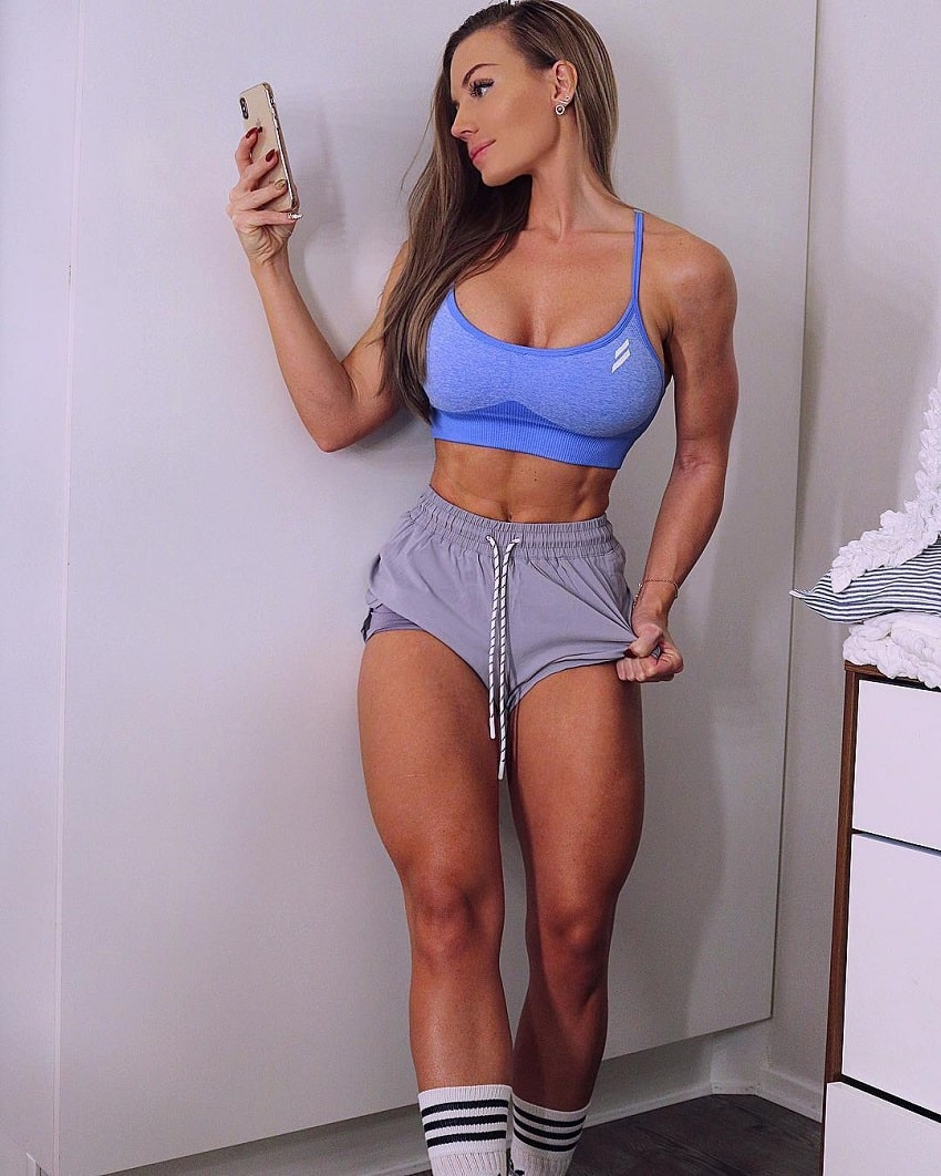 Elin Hedstrom standing in the room wearing grey shorts, looking fit and lean