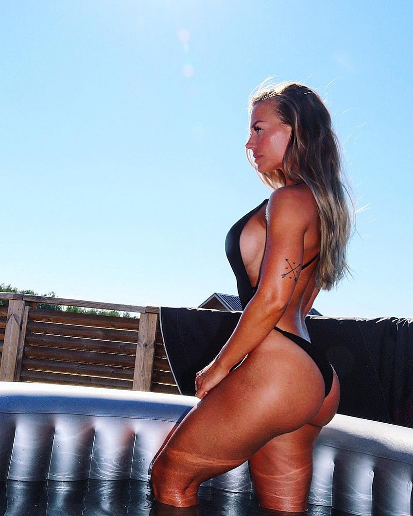 Elin Hedstrom posing on the balcony in her black swimsuit looking curvy