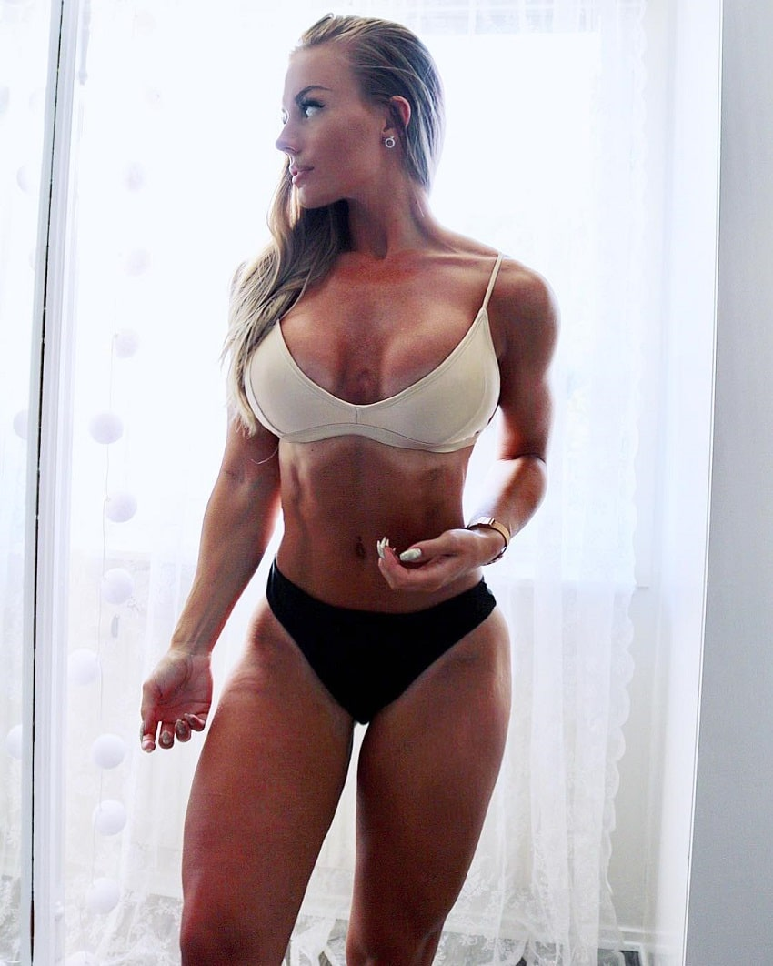 Elin Hedstrom posing in a white bra and black panties, looking fit and lean