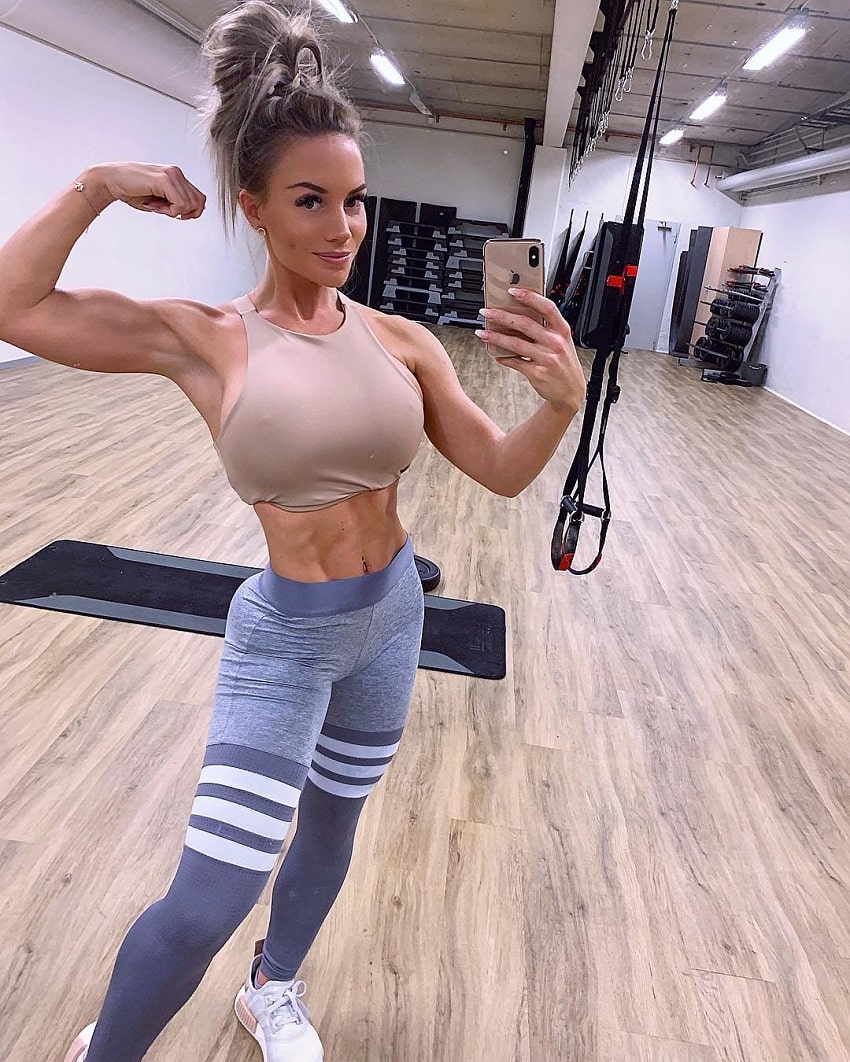 Elin Hedstrom flexing her biceps for the camera looking toned and lean