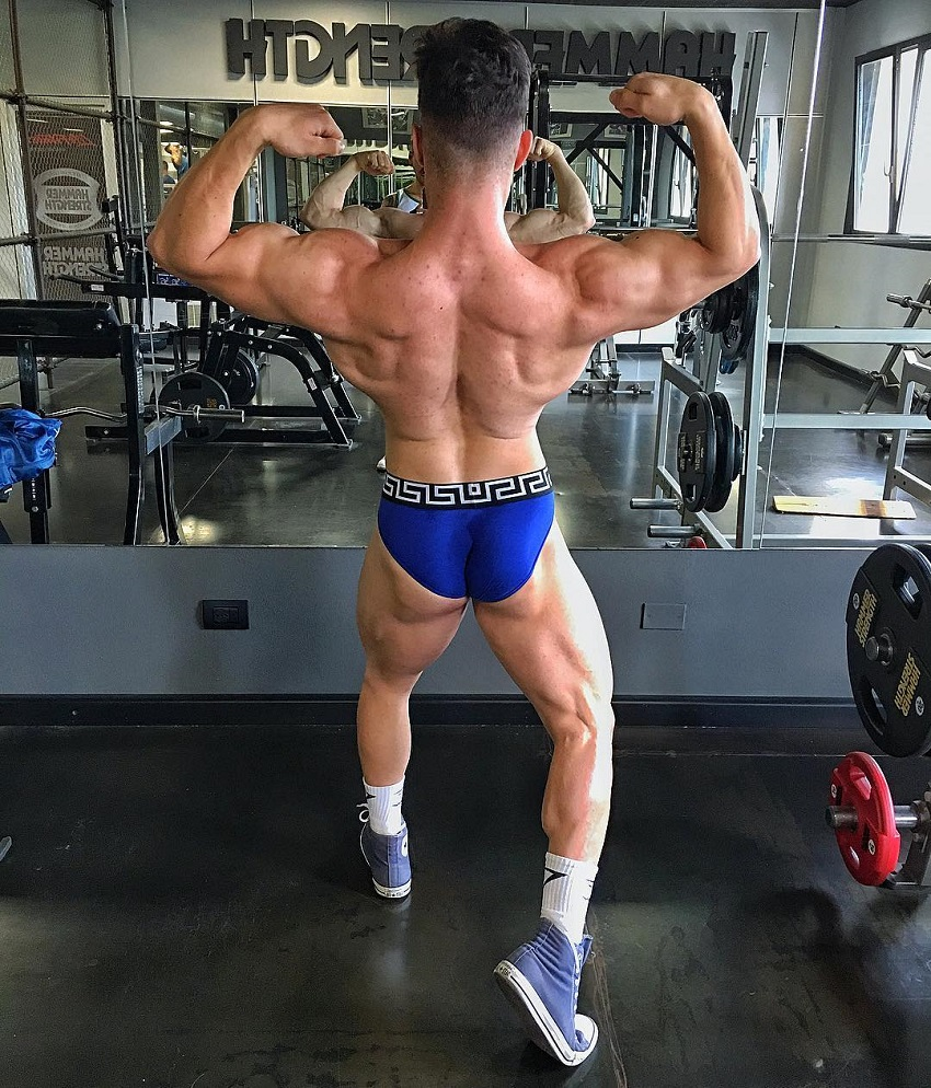Francesco Della Vedova performing a back double biceps pose for the camera, looking ripped and muscular