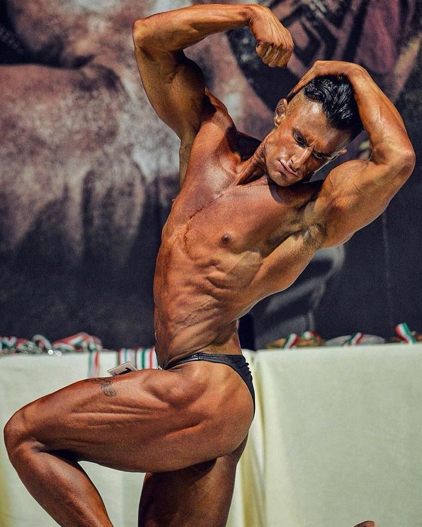 Francesco Della Vedova flexing his muscles on a bodybuilding stage