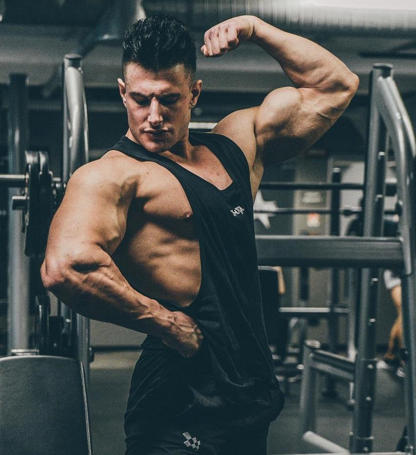 Francesco Della Vedova flexing his biceps wearing a black tank top