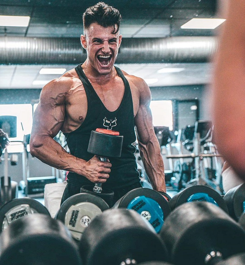 Francesco Della Vedova doing biceps curls while looking at himself in the mirror with a pained grimace
