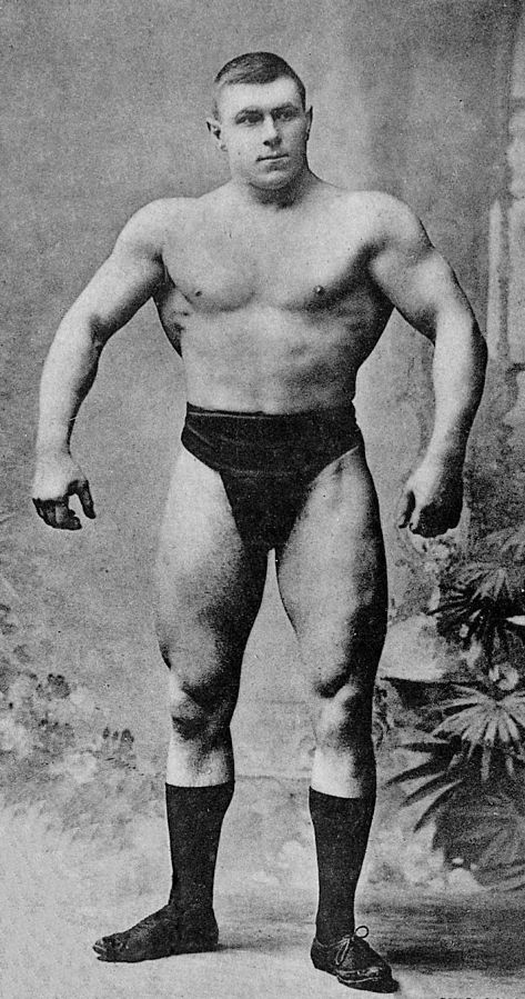 George Hackenschmidt standing shirtless, posing with his lats spread wide, looking muscular and strong