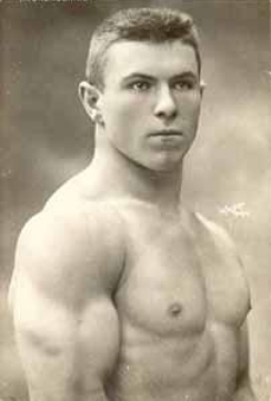 George Hackenschmidt in his youth, standing shirtless showcasing his strong and ripped muscles