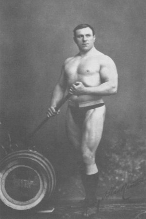 George Hackenschmidt standing shirtless next to a tyre, looking strong and muscular