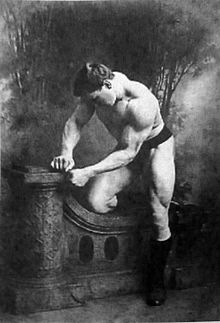 George Hackenschmidt posing shirtless in an old, picturesque black and white photo, showing off his strong muscles