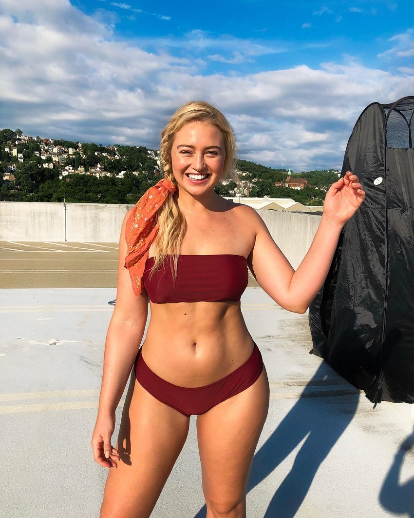 Iskra Lawrence posing outside in a red bikini looking fit