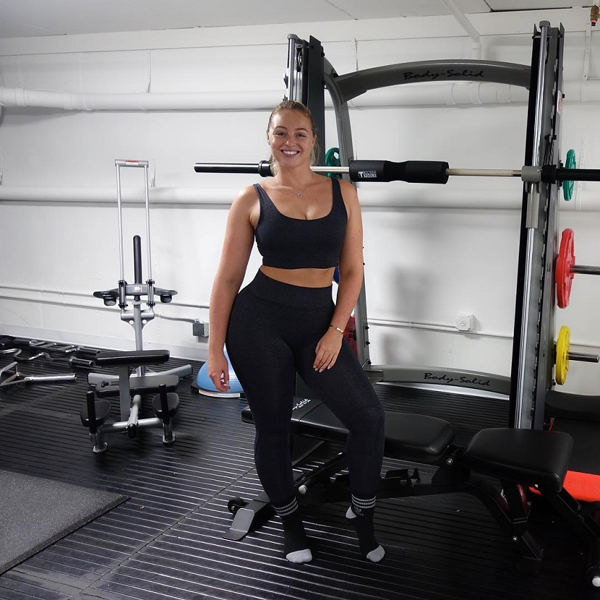 Iskra Lawrence posing in the gym next to weights looking fit and happy