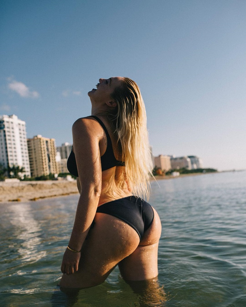 Iskra Lawrence standing half-way in the sea, her glutes looking amazing