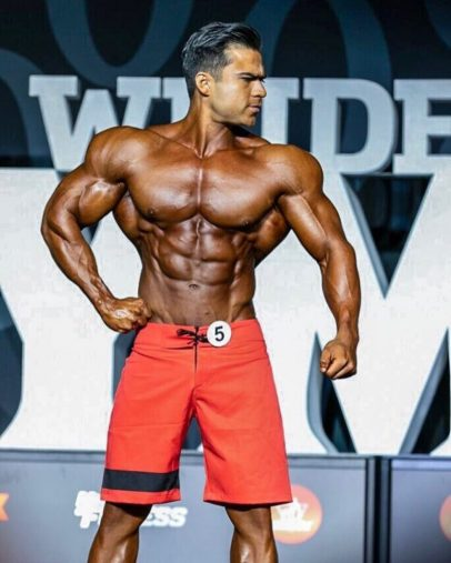 Ismael Martinez posing on the Joe Weider's Mr. Olympia Men's Physique stage, looking ripped and muscular