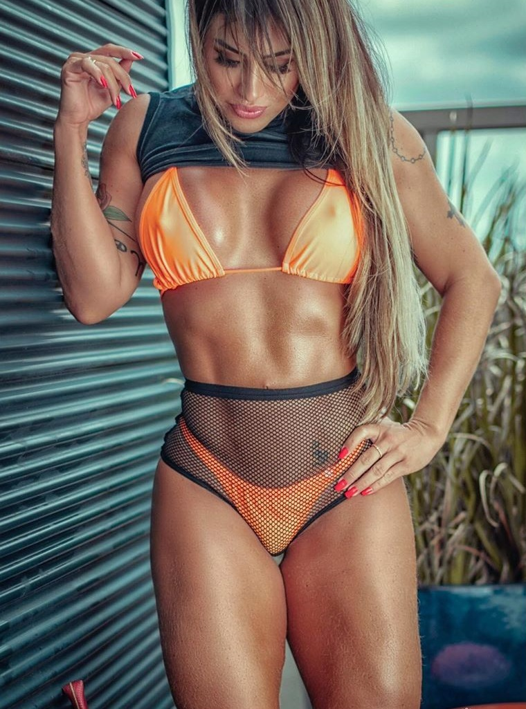 Jaque Khury posing in an orange bikini during a photo shoot, looking lean and toned
