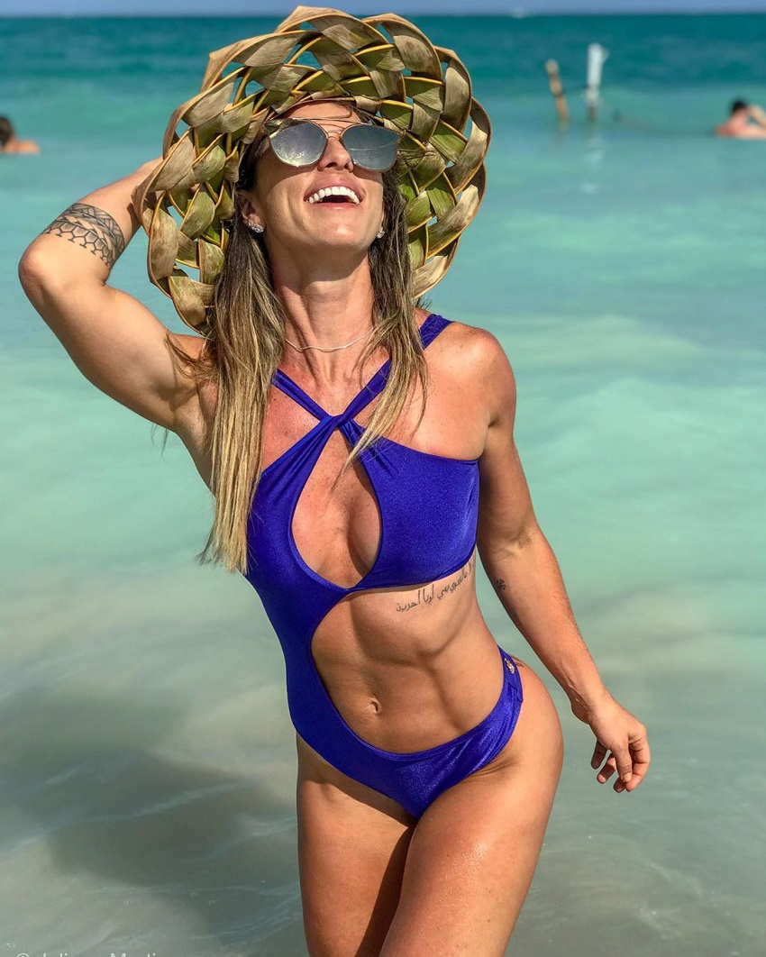 Juliana Martin standing half-way in the sea, looking fit, healthy, and happy
