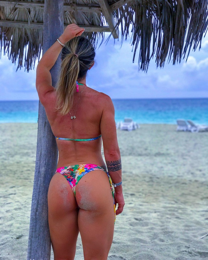 Juliana Martin standing on the beach in a colorful bikini, her glutes looking toned and curvy