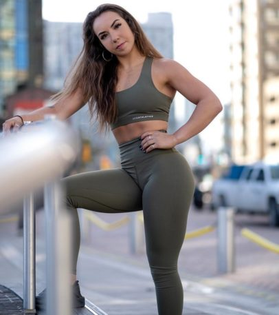 Kenzie Forbes posing in a busy city stress in her gym outfit looking lean and toned