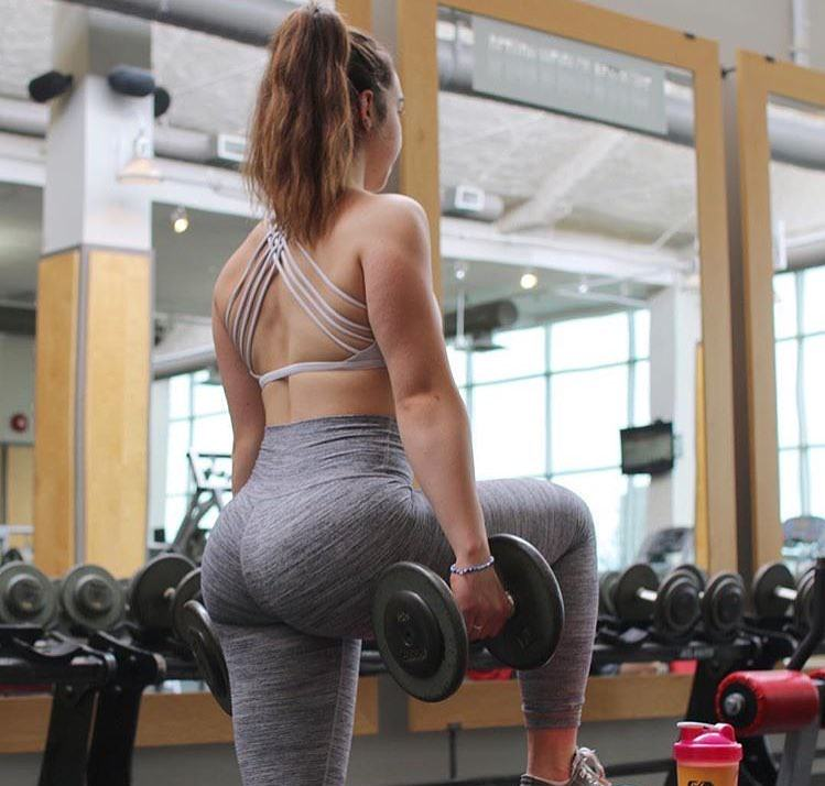 Kenzie Forbes doing lunges with dumbbells in a gym wearing grey leggings, looking curvy and fit