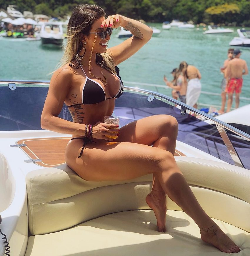 Laleska Bruschi sitting on a boat in a black bikini looking at the distance and smiling