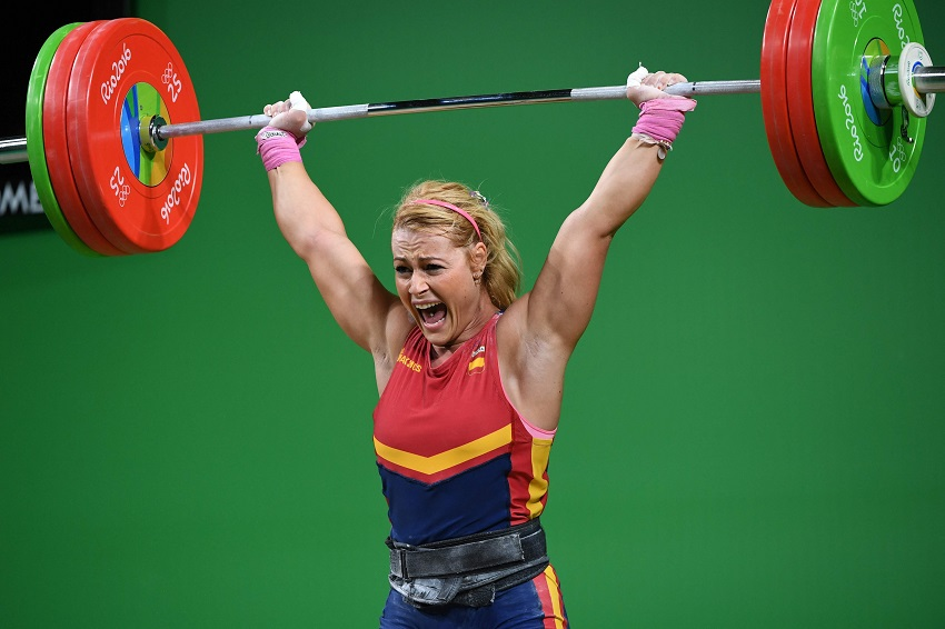 Lidia Valentin Perez performing an extremely heavy overhead press during Olympics weightlifting contest, having a pained grimace