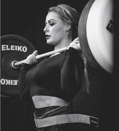 Lidia Valentin Perez lifting a heavy barbell during a weightlifting contest
