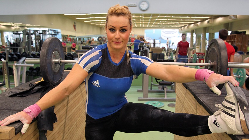 Lidia Valentin Perez stretching in the gym while looking at the camera, looking fit and toned