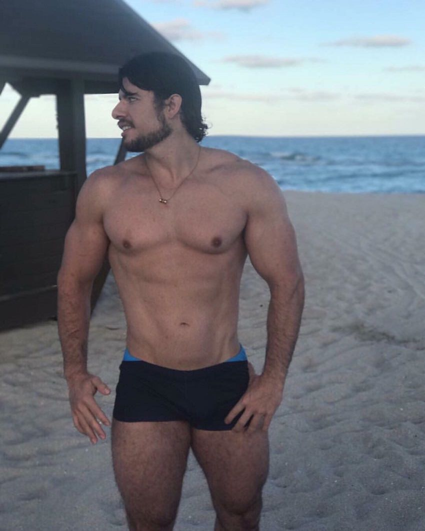 Lucas Giovani standing shirtless on the beach looking fit and lean