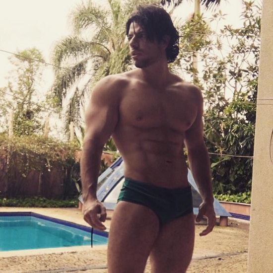Lucas Giovani standing shirtless by the pool looking ripped and muscular