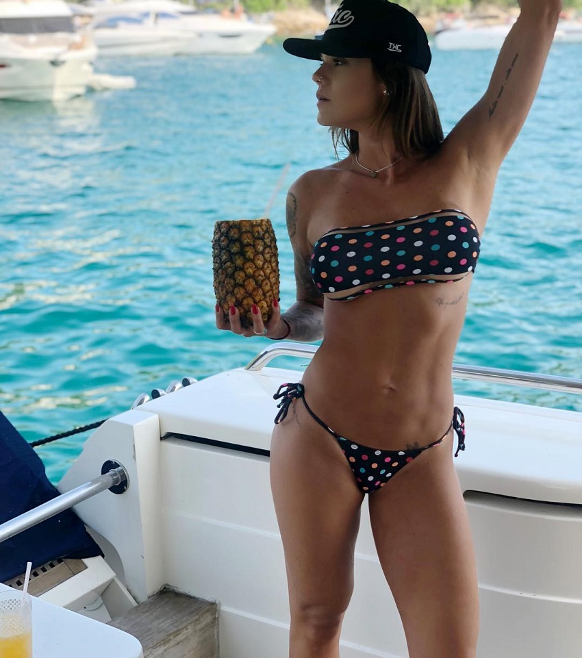 Marcela Moura posing with an ananas gourd on a boat looking fit