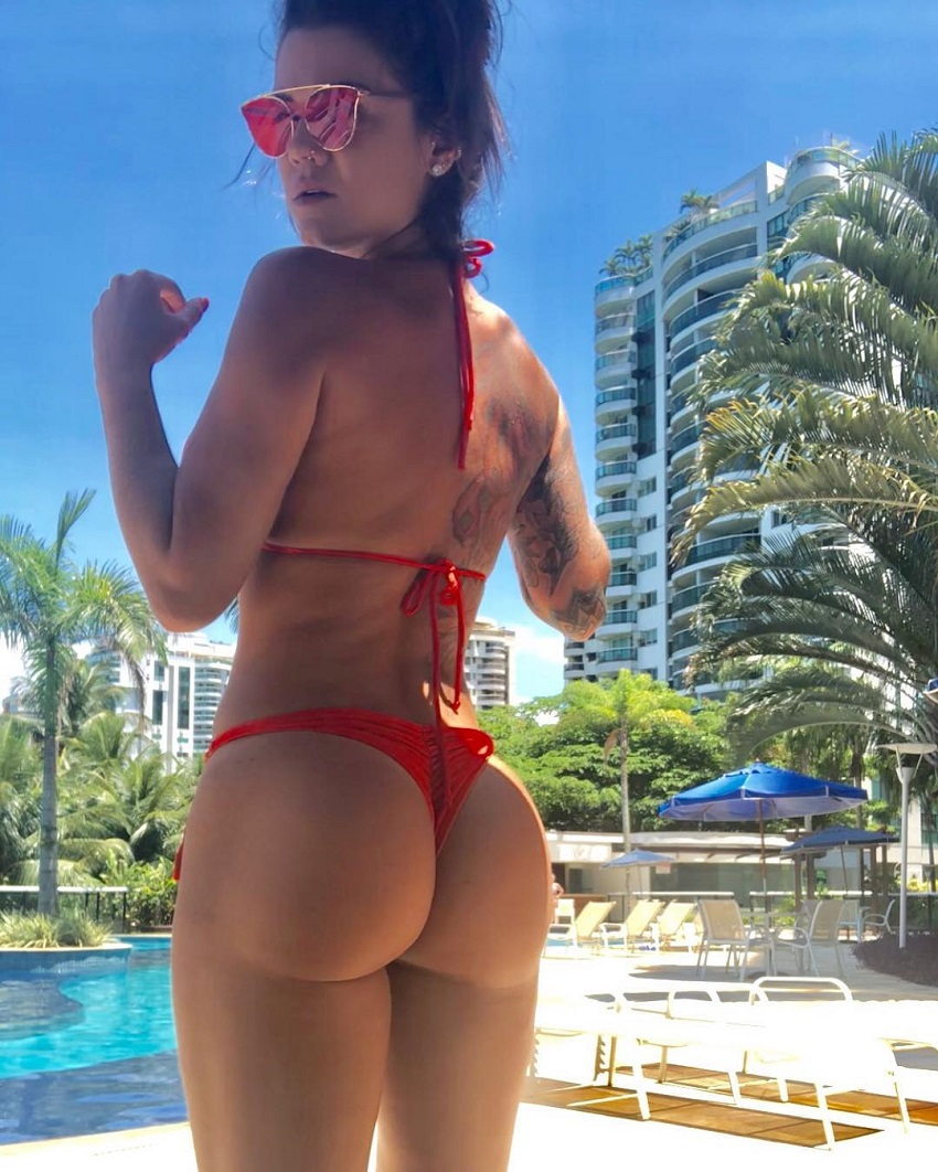 Marcela Moura posing by a pool, her glutes looking amazing