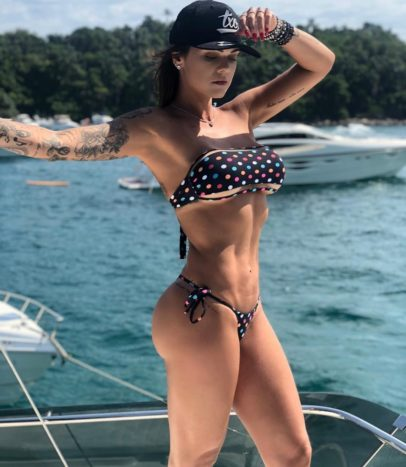 Marcela Moura posing on a boeat looking toned and curvy