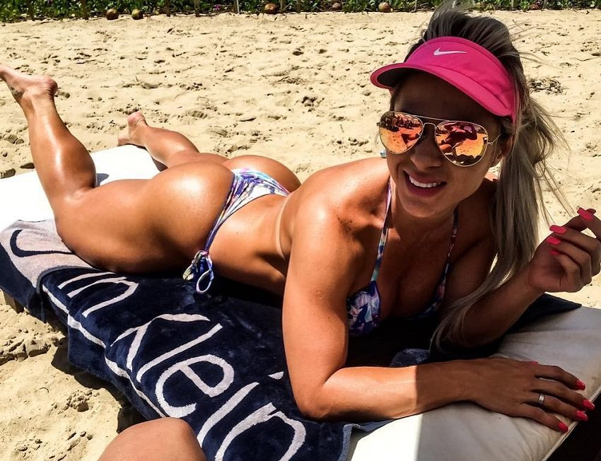 Mari Carvalho lying on a beach in a bikini and with sunglases, looking curvy and fit