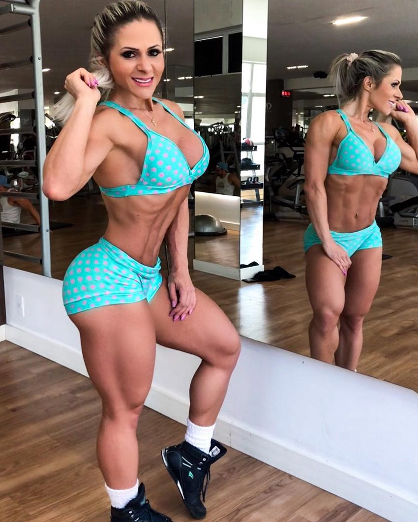 Mari Carvalho standing by a mirror posing for a picture, looking fit and ripped