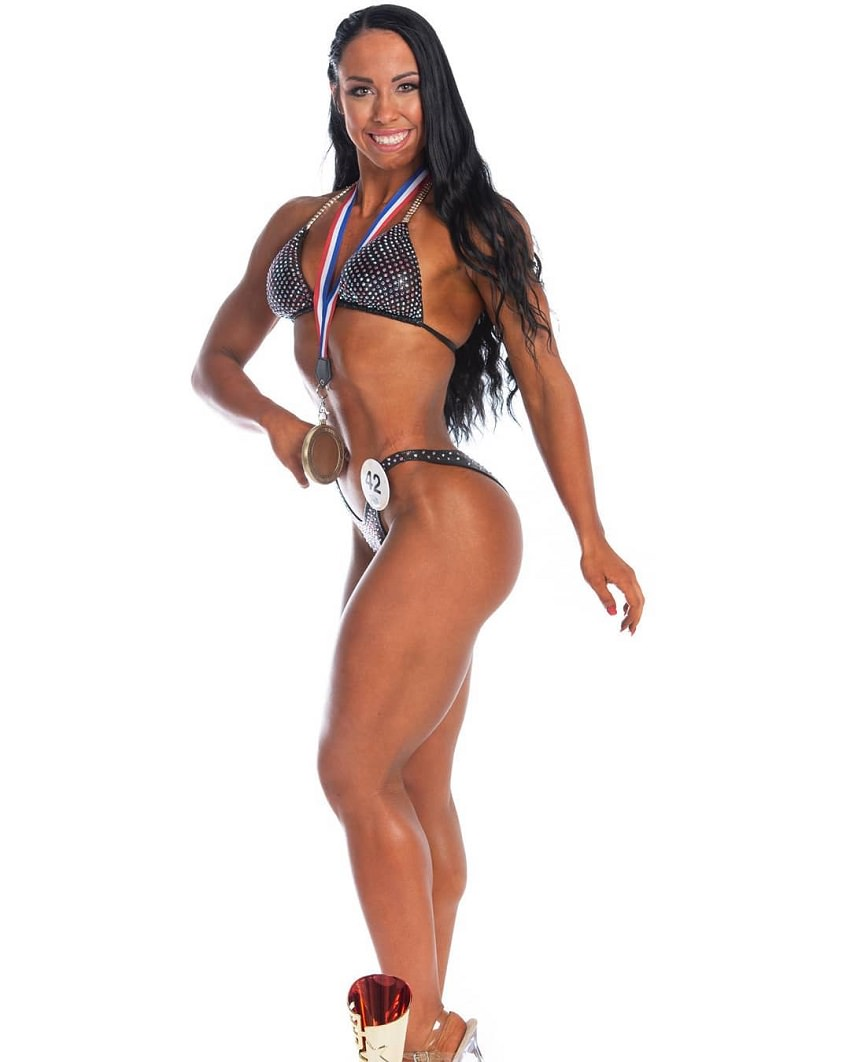 Megane Di Ioia posing in a professional bikini photo shoot with a medal around her neck, looking lean, fit, and tanned up