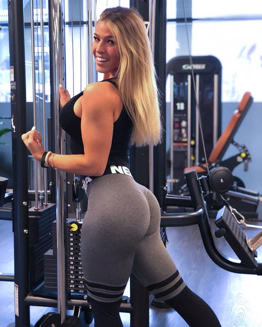 Michelle Bieri posing in the gym showing off her curvy legs and glutes in grey leggings