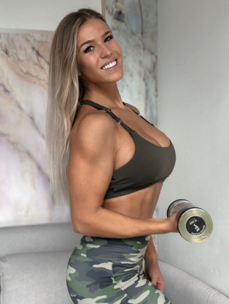 Michelle Bieri posing with a dumbbell looking fit