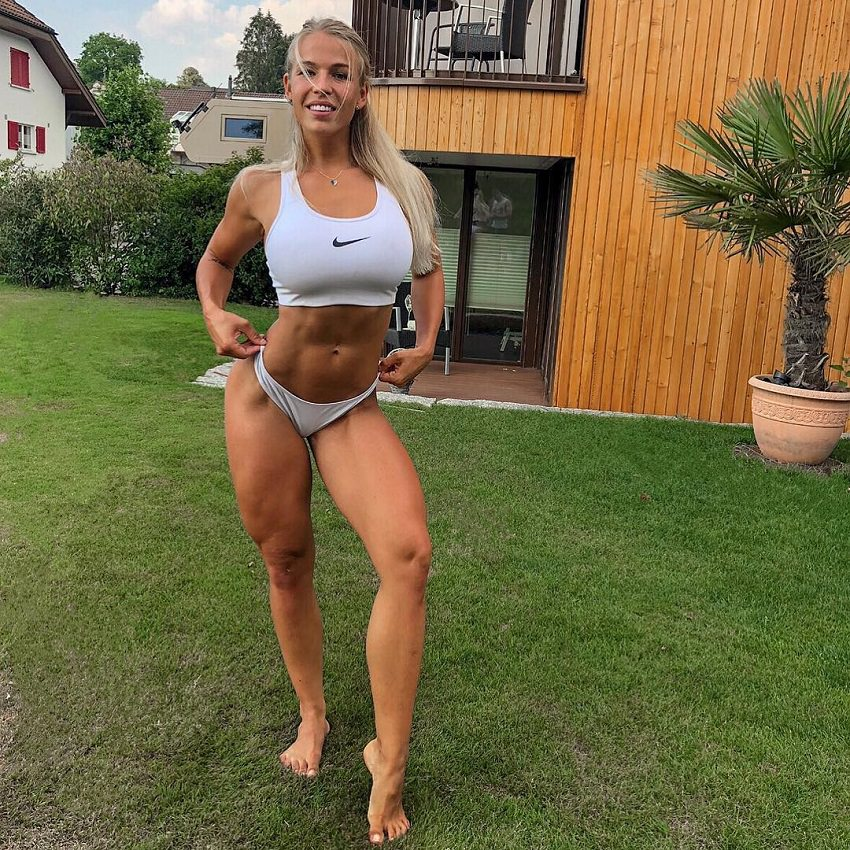 Michelle Bieri standing barefoot on the grass in her backyard, looking fit and toned
