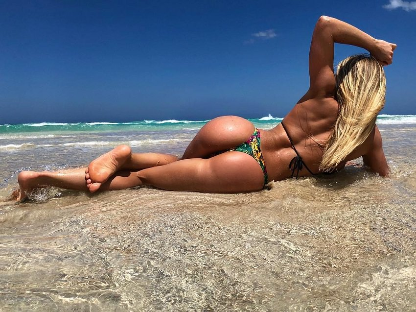 Michelle Bieri lying on the beach her glutes and legs looking fit and toned