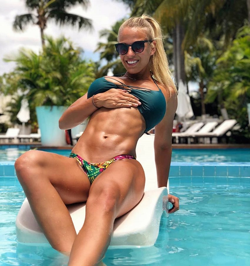 Michelle Bieri showing off her toned abs while lying on a white inflatable pool float, in the pool