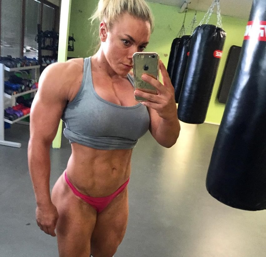 Minna Pajulahti taking a selfie of her muscular and ripped physique in a room full of black boxing bags