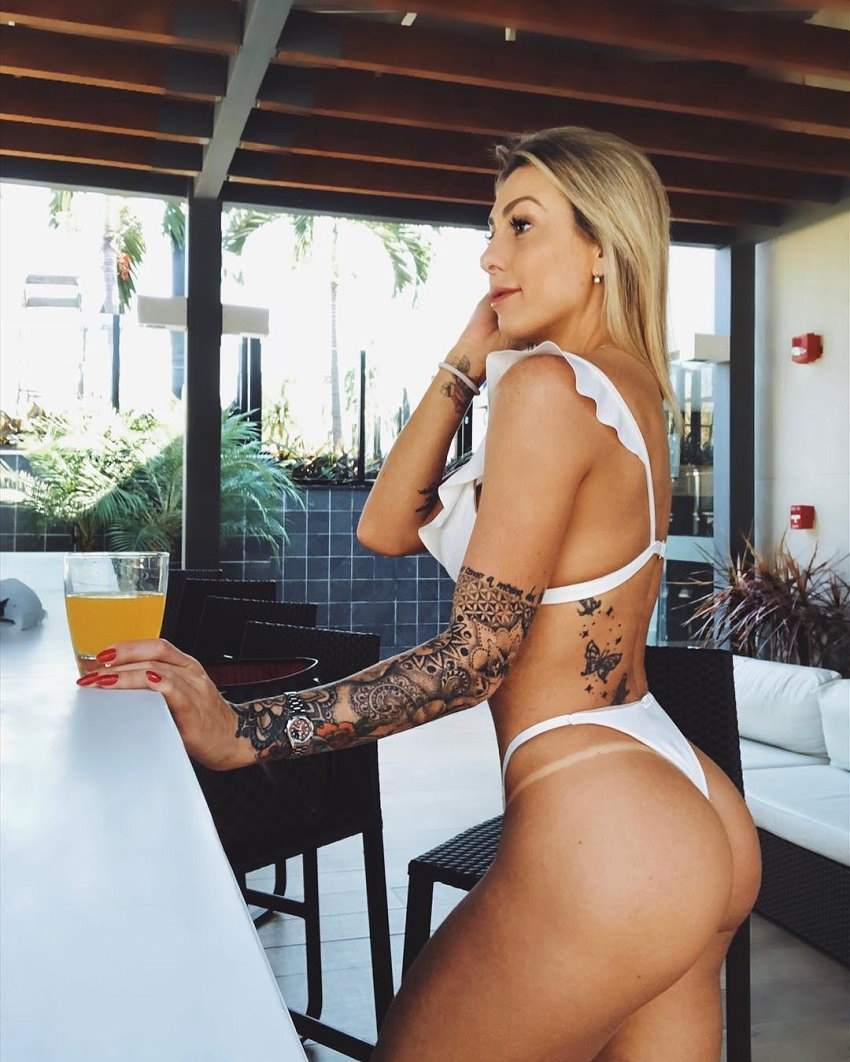 Rafaela Pirola standing by a bar with a glass with fruit juice in her hand, looking fit and toned