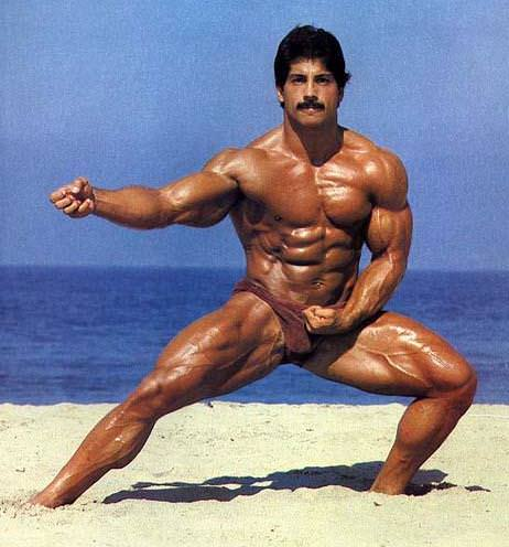 Ray Mentzer standing shirtless in a Martial arts pose on a beach