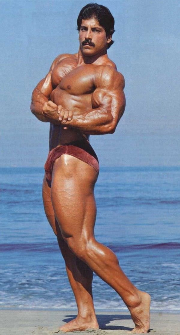 Ray Mentzer doing a shirtless side chest pose during a sunny day on a beach