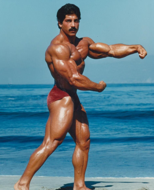 Ray Mentzer flexing shirtless on the beach looking huge and ripped